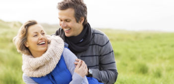 Affectionate mid adult couple in winter wear laughing while embracing. Horizontal shot.